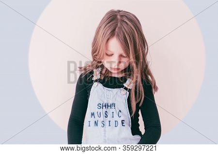 Portrait Of A Young Girl With Long Hair And Closed Eyes Wearing A Dungarees With The Text Shh!! Musi