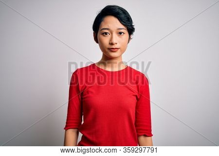 Young beautiful asian girl wearing casual red t-shirt standing over isolated white background Relaxed with serious expression on face. Simple and natural looking at the camera.