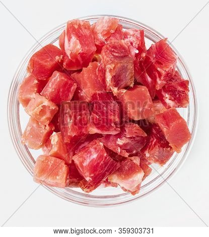 Iberian Ham (serrano) Cut Into Cubes (diced). In Glass Bowl. Isolated On White Background.