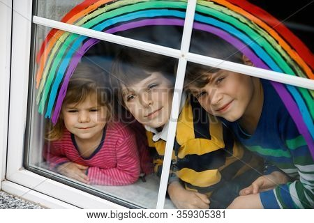 Three Kids, Two School Kids Boys And Toddler Girl With Rainbow Painted With Colorful Window Color Du