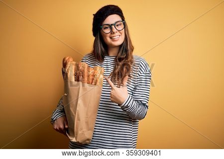 Young beautiful brunette french woman wearing beret holding paper bag with baguettes very happy pointing with hand and finger