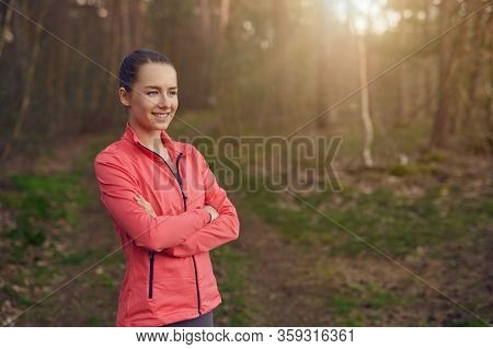 Happy Confident Young Woman With A Friendly Smile Standing With Folded Arms In Woodland Backlit By T