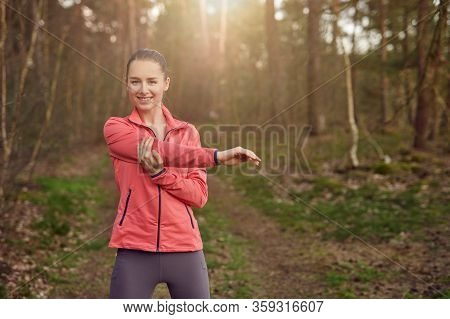 Front View Portrait Of A Happy Fit Woman Stretching Her Arm During Warming Up Exercises Outdoors In