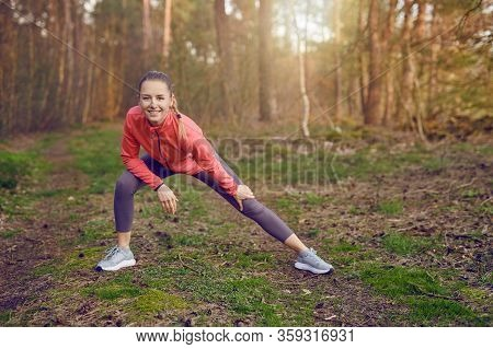 Full Length Portrait Of A Happy  Fit Young Woman Doing Stretching Exercises For Legs And Arms During