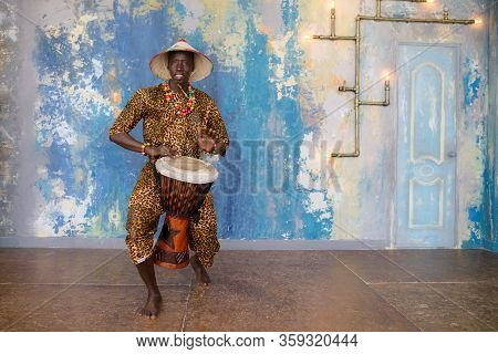 African Man In Traditional Clothes Playing Djembe Drum