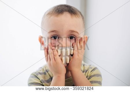 Little Boy Covered His Mouth With Medical Pills, Closeup Portrait, Shocked Or Surprised Toddler