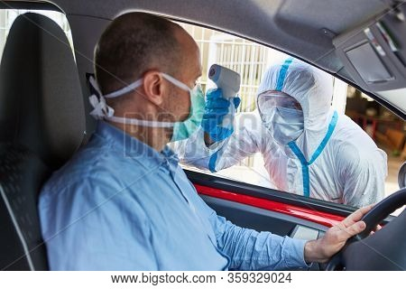 Motorists with contactless fever measure in coronavirus drive-in test station at Covid-19 pandemic