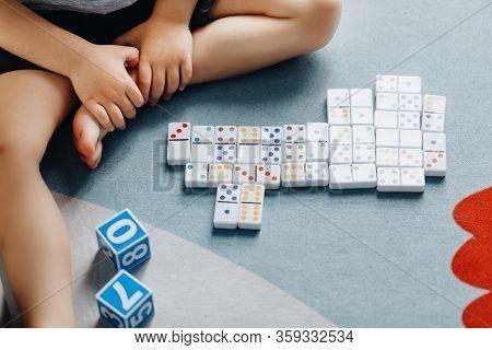 Little Baby Plays Dominoes In His Room On The Floor
