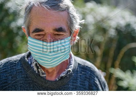 Portrait Of An Old Man, 75 Years Old, In A Medical Mask. Danger Of Coronavirus For The Elderly