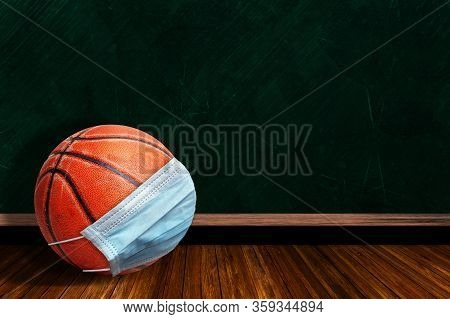 Basketball Wearing Surgical Mask On A Background Chalk Board With Copy Space For Text. Concept Of Co