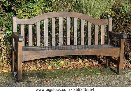 Traditional Wooden Park Seat With Shrub Plants And A Fence Behind Sitting On A Hard Surfaced Path Wi