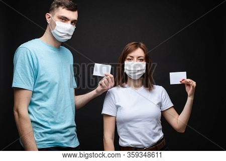 Couple In Masks With Empty Cards. People In Aseptic Masks Holding Two Blank Cards With Place For Tex