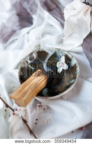 Composition With Peruvian Palo Santo Holy Wood On Handmade Ceramic Plate, White Candle And Bottle Wi