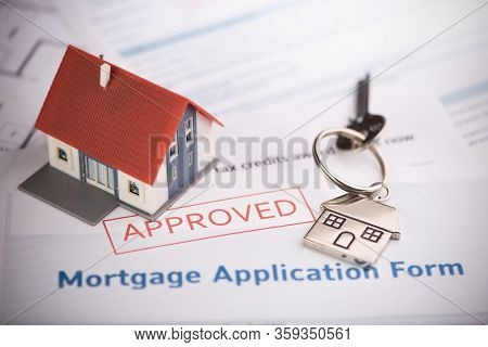An Approved Mortgage Loan Application Form With House Key And Rubber Stamp Close Up