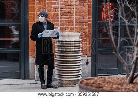Horizontal Shot Of Young Man Looks Aside, Wears Medical Rubber Gloves And Face Mask, Looks Aside, Ho