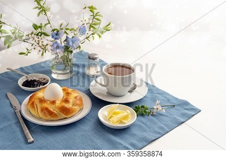 Easter Yeast Bread Plaited To A Nest With An Egg, Coffee, Butter And Jam On A Blue Napkin And A Whit