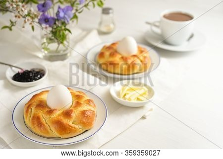 Easter Yeast Bread Plaited In Nest Form With Eggs, Coffee, Butter, Jam And Flowers On A White Table,
