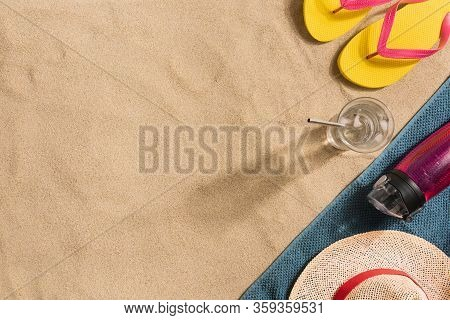 Summer Vacation Composition. Flip Flops, Water Bottle And Straw Hat On Sand Background. Harsh Light