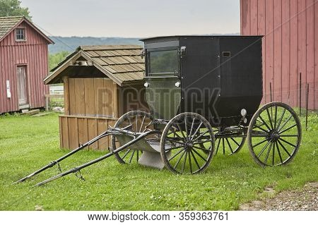 Amish Buggy Parked Next To Red Barn