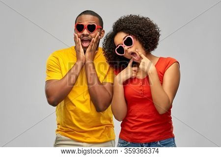 love, relationships and valentines day concept - happy smiling african american couple in heart shaped sunglasses making silly faces over grey background