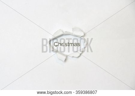 Word Christmas On White Isolated Background, The Inscription Through The Wound Hole In The Paper. St