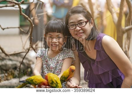 Beautiful Childhood, Asian Child Girl And Mother Together In Zoo, Feeding Small Birds Or Sun Conure