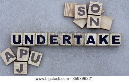 Concept Of The Word Undertake On Cubes On A Gray Background