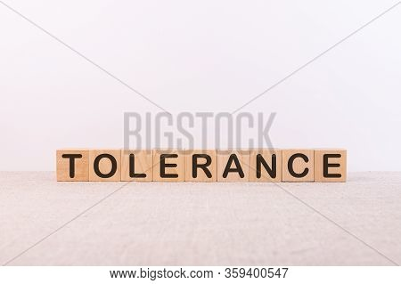 Tolerance Word Concept Written On Wooden Cubes Lying On A Light Table And Light Background.