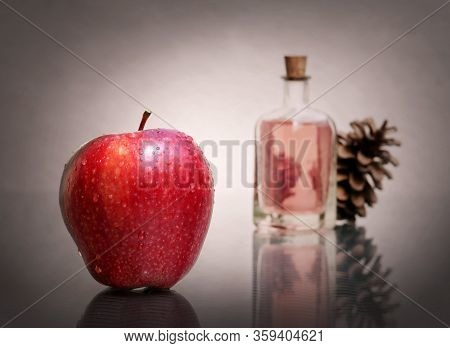 Still Life With Red Ripe Apple, Essential Aroma Oil In Vintage Glass Bottle And Pine Cone Against A