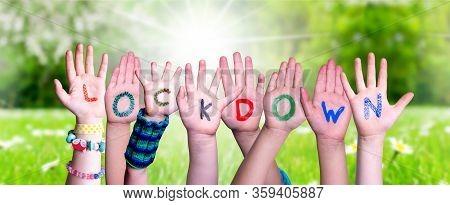 Kids Hands Holding Word Lockdown, Grass Meadow