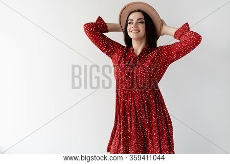 Young Beautiful And Stylish Woman On A White Background. Red Sundress And Female Brown Hat. Place Fo