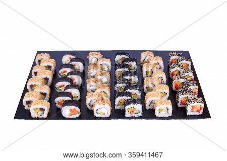 Sushi Set Spicy Mix Rolls With Fresh Ingredients On Black Stone Isolated On White Background. Sushi