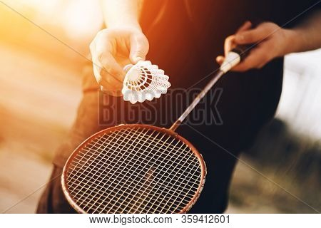 A Man Is Holding A Red Badminton Racket And A White Shuttlecock That Is Going To Be Thrown Into The