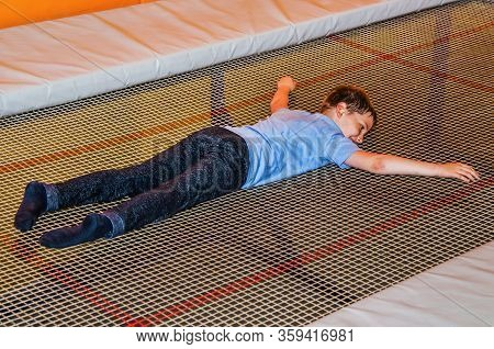 Boy Lies On A Trampoline In A Trampoline Park