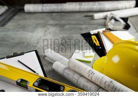 Contractor Concept. Tool Kit Of The Contractor: Yellow Hardhat, Libella, Hand Saw. Plans And Noteboo