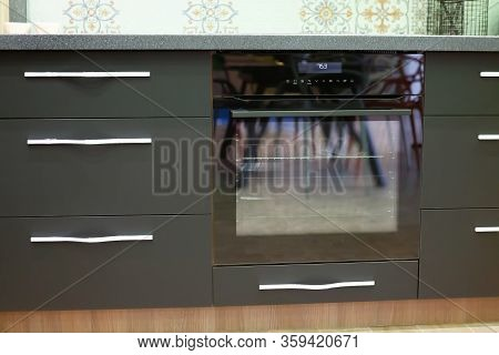 Built-in Oven In The Kitchen Countertop. Built-in Appliances In The Kitchen. Cabinets Are Gray, Blac
