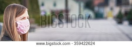 Young Woman With Hand Made Face Nose Mouth Mask Portrait, Blurred Empty City Square Behind Her. Wide