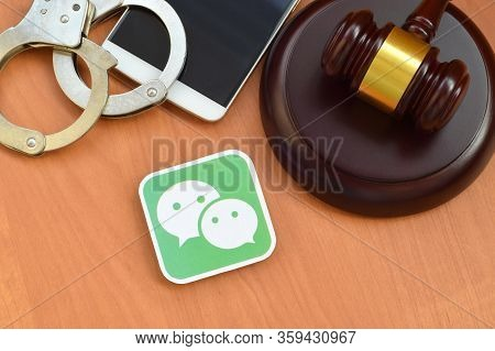 Wechat Paper Logo Lies With Wooden Judge Gavel, Smartphone And Handcuffs. Entertainment Lawsuit Conc