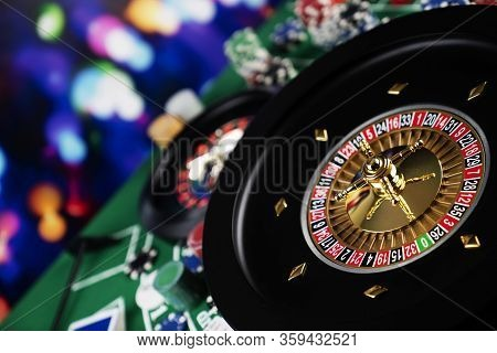 Roulette Table In Casino. Casino Felt Green Table With Red And Black Numbers. Stack Of Poker Chips.