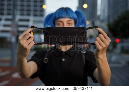 Young Female Using Medical Mask In City, Stylish Trendy Girl With Blue Hair Wearing Fashionable Prot