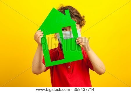 The Child Hid In The House. Quarantine Coronavirus. A Little Boy In A Medical Mask And A Red Shirt H