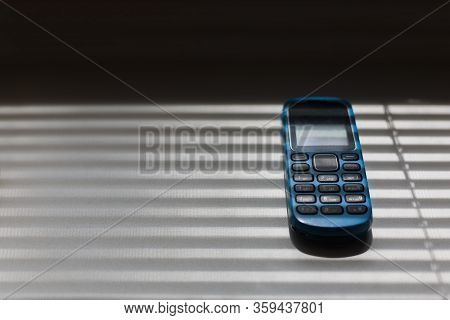 Obsolete Mobile Qwerty Phone On The Windowsill. On The Phone Lying On The Windowsill, Rays Of Light