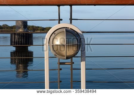 Light Fixture On A Ship Railing, Blue Sky And Still Waters, Horizontal Aspect