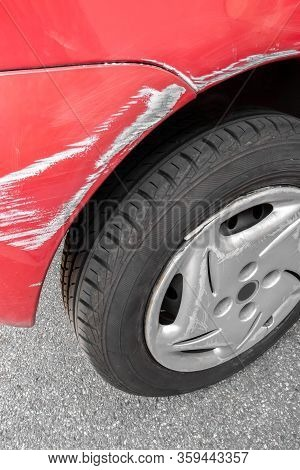 Car Body Damage. Dents And Scratches On The Red Car Paint.