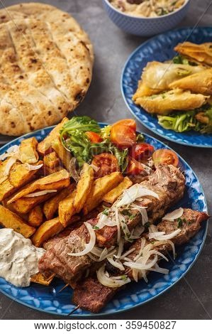 Souvlaki Served With Fried Potatoes, Tzatziki Dip And Pita Bread, Greek Cuisine.