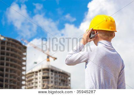 Boy in helmet on building under construction background