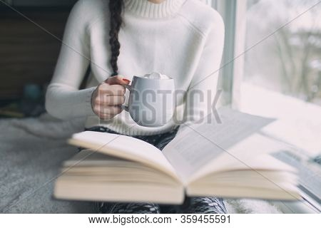 Woman by the window holding cup of hot drink and a book, story reading concept