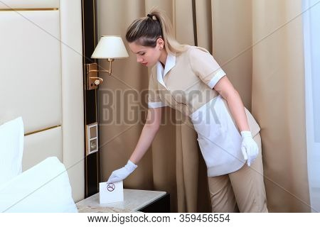A Maid In White Gloves And A Uniform Puts A Sign On The Nightstand Reminding Of The Smoking Ban. Pho