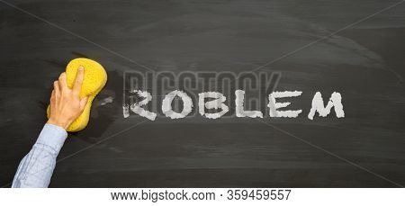 Man's hand with a sponge erases the written word PROBLEM from the blackboard