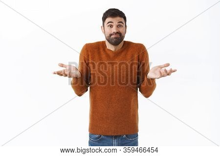 Portrait Of Indecisive, Clueless Attractive Bearded Man In Brown Sweatshirt, Dont Know, Spread Hands